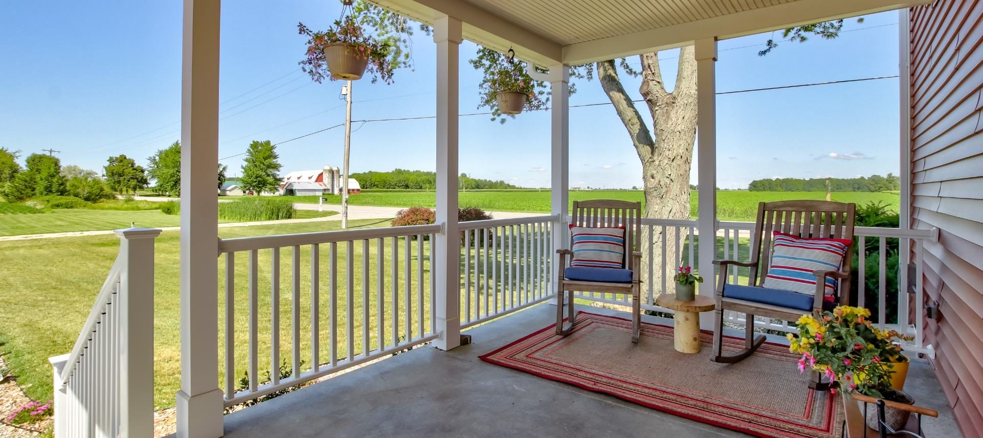 Front porch of property with two wooden rockers, area rug, and hanging flower baskets