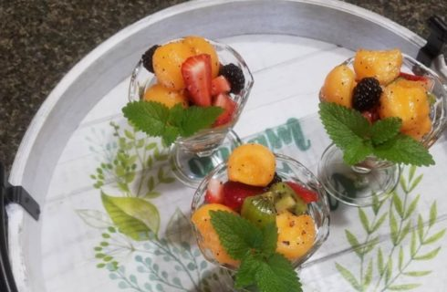 Three glass fruit cups filled with melon balls, sliced strawberries, blackberries, and kiwi