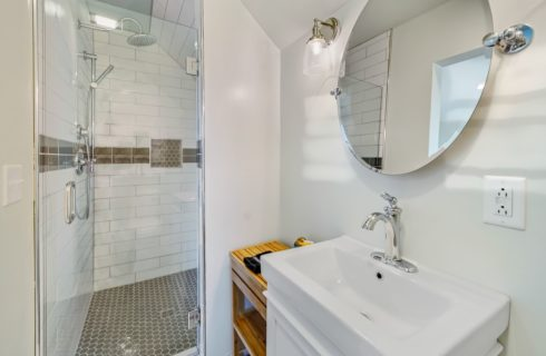 Bathroom with tiled walk-in-shower, white vanity with white sink, and large round mirror