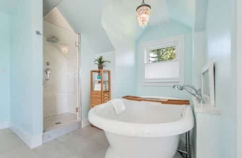 Bathroom area with light blue walls, tile flooring, tiled walk-in-shower, large white tub