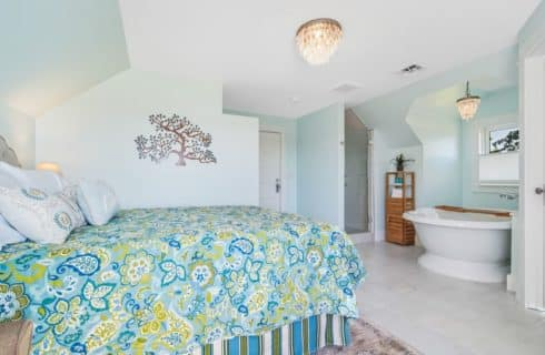 Bedroom with a light shade of blue on the walls, bed with green and blue bedding, and a large white bathtub
