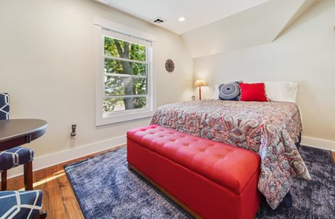 Bedroom with light cream walls, hardwood flooring, bed with navy, red, and tan paisley bedding, and large red cushioned storage box at the foot of the bed