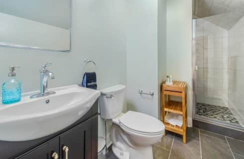 Bathroom with light shade of blue walls, tiled floor, dark wooden vanity with white sink, and tiled walk-in-shower